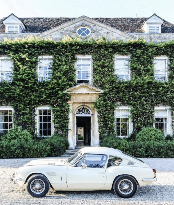 ivy covered house with sportscar